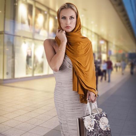 lovely elegant lady with orange scarf and shopping bag over white