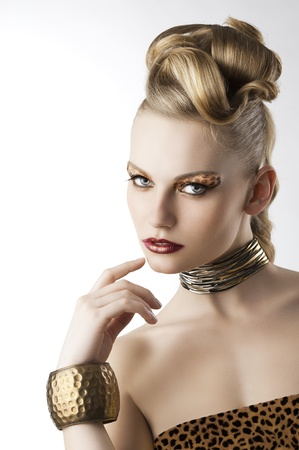 fashion beauty portarit of blond young cute girl with creative hair style and leopard make up, she is turned of three quarters looks in to the lens and has the right hand near her mouth