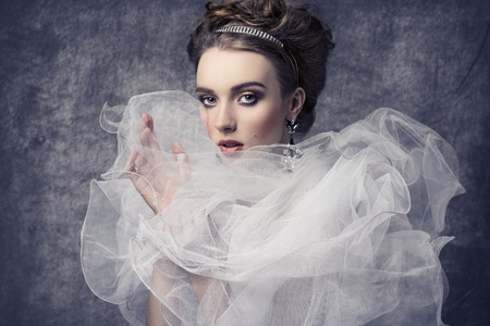 Foto de fashion shoot of pretty woman with romantic retro dame style. Wearing baroque dress with frill veil collar, precious earrings and tiara in the hair-style, elegant make-up - Imagen libre de derechos