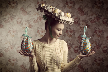 Photo pour creative portrait of beautiful brunette woman with yellow clothes posing with easter eggs in carton box on the head. Bizarre hat, old fashion - image libre de droit