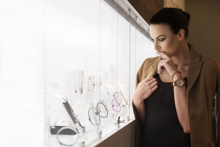 Photo pour pretty lady , inside a jewellery near a window shop , thinking what to buy , shot in natural ambient light . - image libre de droit