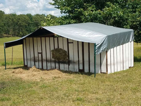 Photo pour Sheep shelter made from reclaimed redwood siding with silver tarp roof - image libre de droit