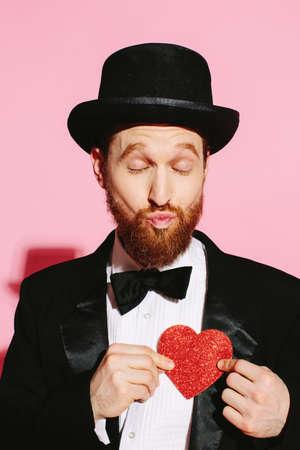 Foto de Funny Valentine- man pouting and holding a rred heart - Imagen libre de derechos