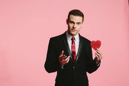 Foto de Handsome man in a black suit holding a red heart for Valentine's Day - Imagen libre de derechos