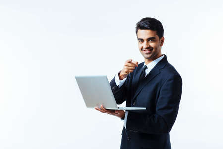 Photo pour Portrait of a confident young man entrepreneur in business suit holding a laptop and pointing at camera,  isolated on white background - image libre de droit