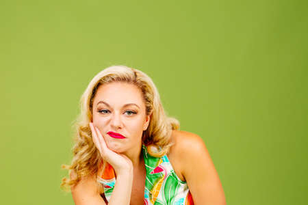 Photo for Portrait of a bored and unhappy blonde woman, isolated on green studio background - Royalty Free Image