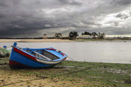 Photo pour Traditional boat of Lisbon area, moored on the beach, at the low tide - image libre de droit