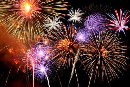 Photo pour Fireworks of various colors bursting against a black background - image libre de droit