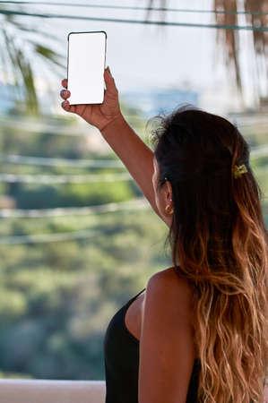 Foto de smartphone screen cutout, latin woman with using smartphone, augmented reality, taking selfi, - Imagen libre de derechos