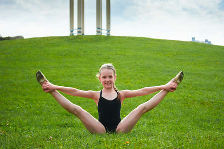 Young beautiful preteen girl doing gymnastic stretch yoga outdoors in park