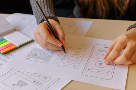 Photo pour Designer wireframing a mobile App on wooden desk - image libre de droit