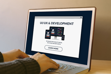 Foto de UI/UX design and development concept on laptop computer screen on wooden table. Hands typing on a keyboard. All screen content is designed by me. - Imagen libre de derechos