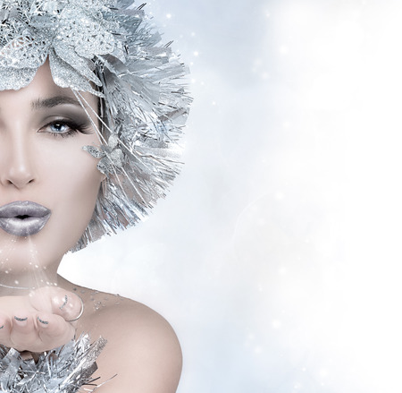 Beauty festive fashion. Christmas girl sending a kiss. Magic winter woman with silver stylism. Vogue style model blowing her hand. Sending good wishes. Half face portrait with copy space for text