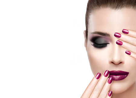 Beauty and Makeup concept. Beautiful fashion model woman with hands on face covering half mouth and one eye. Perfect skin. Professional manicure and makeup. smoky eyes. Fashionable eyelashes. High fashion portrait isolated on white with copy space for tex