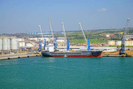 Foto per CIVITAVECCHIA, ITALY - APR 21, 2018 - Freighter in working container harbor of Civitavecchia, Italy - Immagine Royalty Free