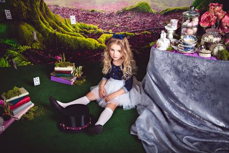 Foto de Little sitting on the floor girl in a beautiful dress in the image of Alice in Wonderland and magician hat in front of her - Imagen libre de derechos