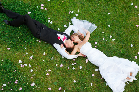 Photo for Happy wedding couple lying on green grass at the summer time - Royalty Free Image