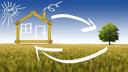 Foto de Wooden yellow meter tool forming a ecologic house in the countryside - Imagen libre de derechos