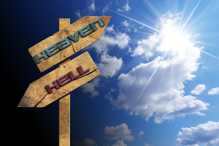 Foto de Wooden directional sign with two arrows in opposite direction with text heaven and hell on blue sky with clouds and sun rays - Imagen libre de derechos