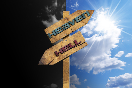 Foto de Wooden directional sign with two arrows in opposite direction with text heaven and hell on blue and black sky with clouds and sun rays - Imagen libre de derechos