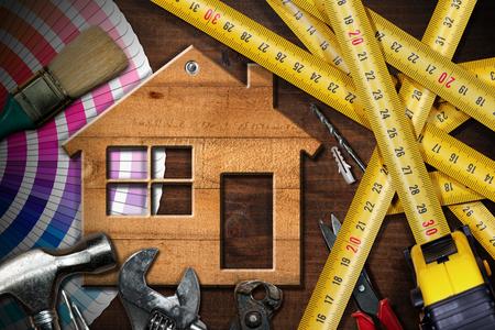 Photo pour Home improvement concept - Wooden model house on a work table with tools - image libre de droit