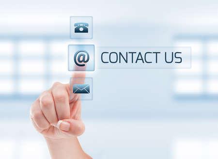 Photo pour Female hand touching contact us button. Futuristic contact us concept on light blue - image libre de droit