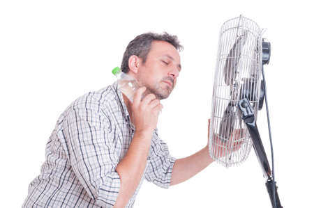 Photo pour Man cooling down in front of blowing fan holding a bottle of cold water on the neck - image libre de droit