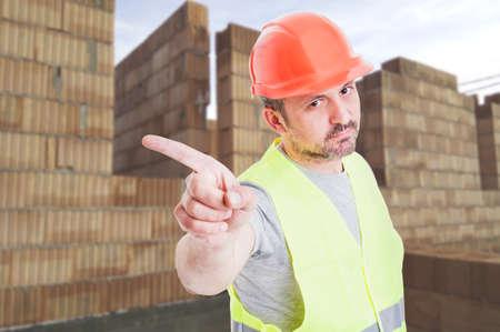 Foto de Serious builder in protection equipment doing a refusal gesture while standing on construction site - Imagen libre de derechos