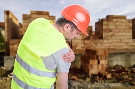 Photo pour Constructor suffering from shoulder pain or having an accident on outdoor  construction workplace - image libre de droit