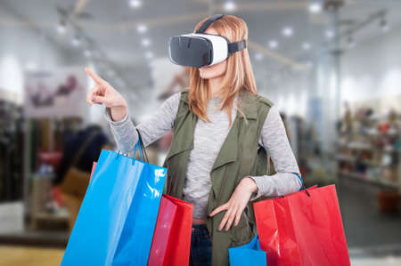Foto de Woman customer experience virtual shopping thru modern headset and pointing finger at something - Imagen libre de derechos