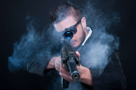 Foto de Mafia criminal aiming weapon at you thru smoke on black background - Imagen libre de derechos