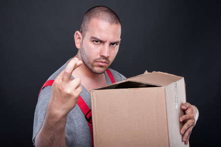Photo for Mover man holding box wising bad luck with fingers crossed on black background - Royalty Free Image