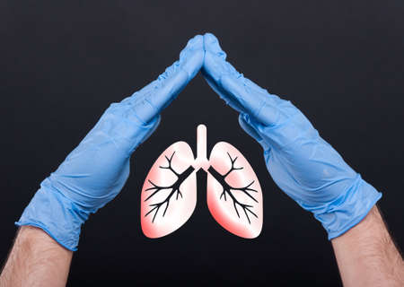 Foto per Medical assistant holding lungs between hands protecting from pulmonary disease isolated on black background - Immagine Royalty Free