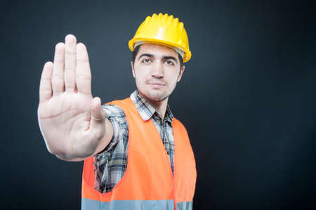 Photo pour Constructor wearing equipment showing stop gesture on black background with copypsace advertising area - image libre de droit