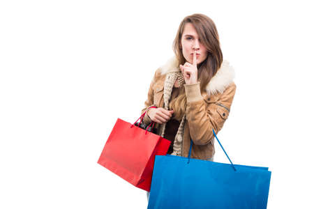 Foto de Stylish shopping girl indicate silence gesture with finger on lips isolated on white background - Imagen libre de derechos
