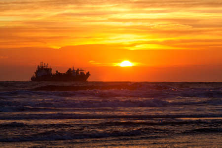 ship silhouette on North sea at sunset, Netherlands
