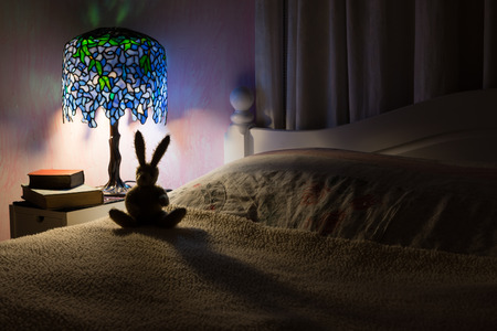 Photo for Bedroom interior at night. A dark room illuminated by a Tiffany style lamp silhouetting a toy rabbit.  Story time at bedtime concept. - Royalty Free Image