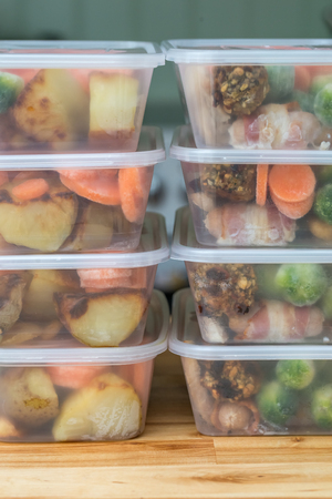 Foto de Meal prep. Stack of home cooked roast chicken dinners in containers ready to be frozen for later use. Vertical. - Imagen libre de derechos