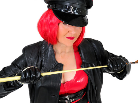 Foto de Dominant woman wearing latex and leather, red and black military clothes including gloves, cap and coat. In a short red wig and holding a whip. Fetish cosplay. White background. - Imagen libre de derechos