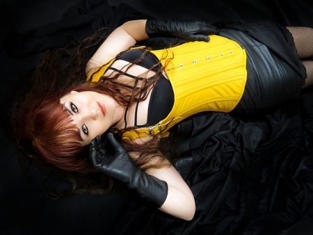 Foto de Attractive woman in yellow corset, lying down viewed from above. Black background. - Imagen libre de derechos
