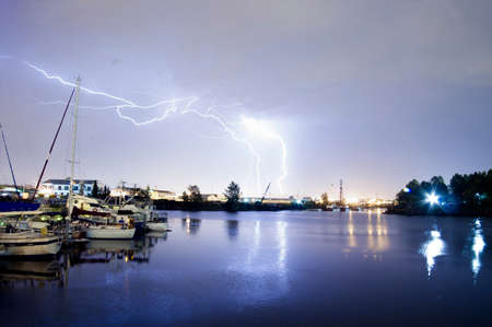 Lightning strikes over the water and marina in Tacoma