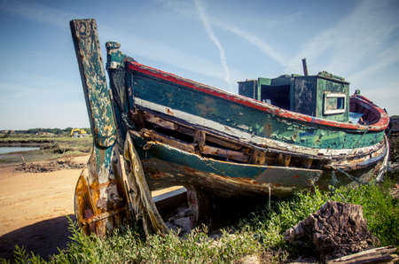 Foto de The remains of an old fishing boat rotting on the river shore - Imagen libre de derechos