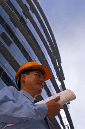 Asian male in a hard-hat holding some floor plans on his way out to a construction site