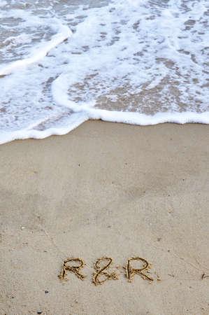Photo pour R&R written on sand - image libre de droit