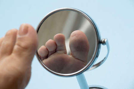 Photo pour Person looking at the sole of the foot in a mirror, to check if there is no diabetic foot, as possible sores - image libre de droit