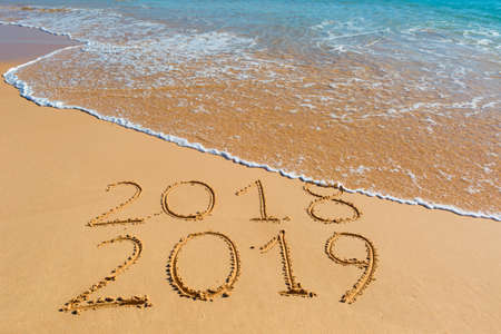 Photo pour 2018 2019 inscription written in the wet yellow beach sand being washed with ocean water wave. Concept of celebrating the New Year at some exotic place. - image libre de droit