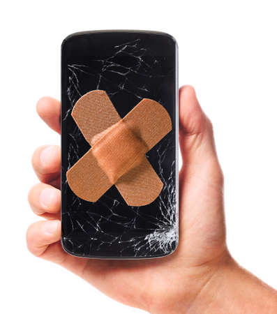 Foto de male hand is holding modern smartphone with cracked screen in one corner healed with plaster, isolated on white background - Imagen libre de derechos