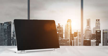 Foto de Laptop on table in office with panoramic sunset view of modern downtown skyscrapers at business district, blank screen - Imagen libre de derechos