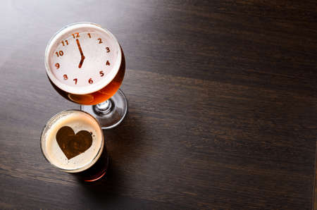 Foto de Heart and clock silhouettes in two glasses of fresh beer on pub table, view from above - Imagen libre de derechos