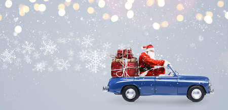Photo for Santa Claus on car delivering Christmas or New Year gifts at snowy gray background - Royalty Free Image